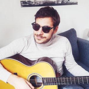 Kai Kortus sitzt mit seiner Gitarre in der Hand