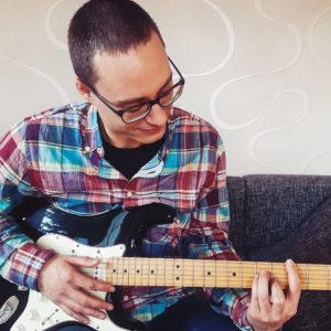 Konstantin sitzt mit seiner E-Gitarre in der Hand